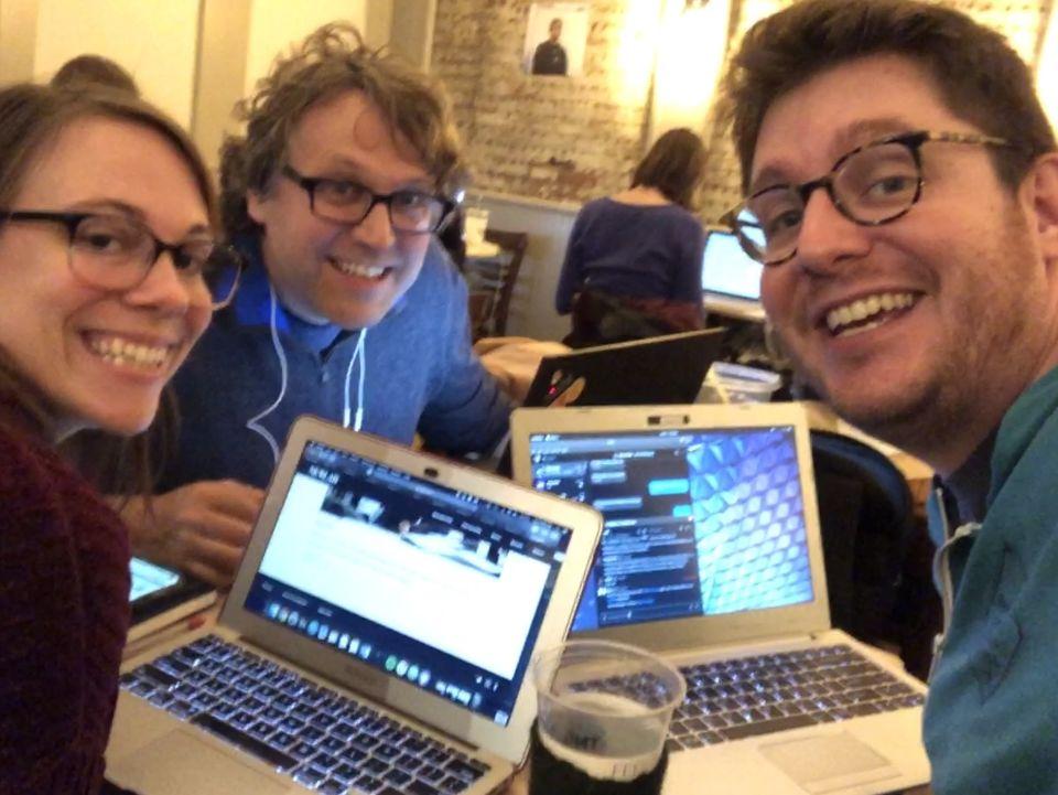 Three people crowded around laptops look into the camera, with toothy grins on their faces.