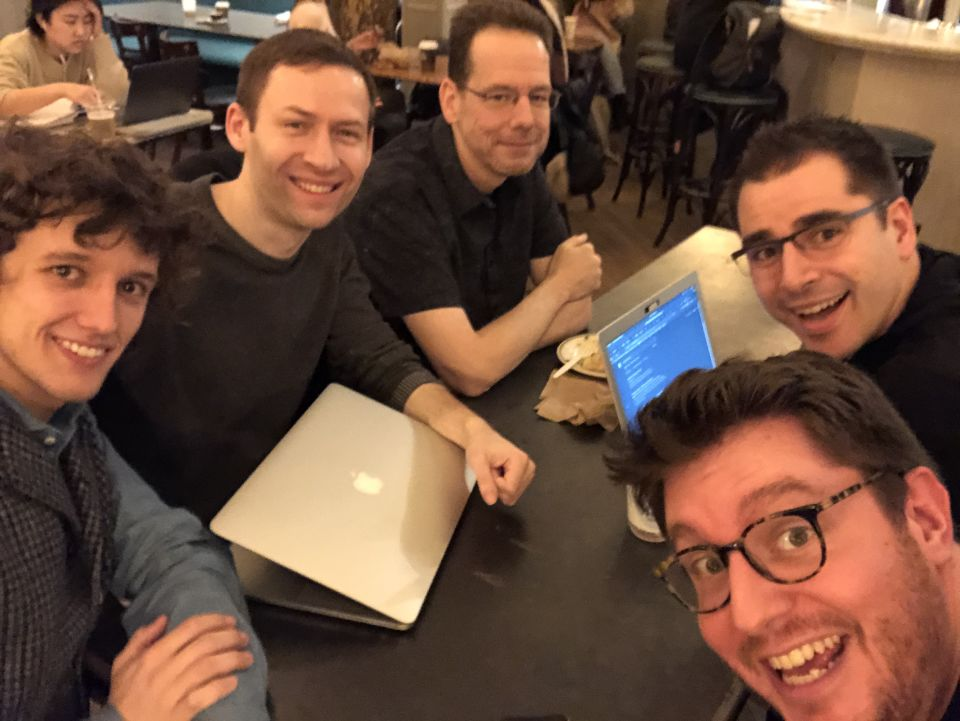 5 attendees smile at the camera, huddled around a small table with laptops on it in a busy coffee shop